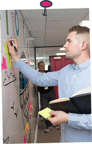 A man putting a post-it note on a whiteboard whilst holding a notepad during a training session
